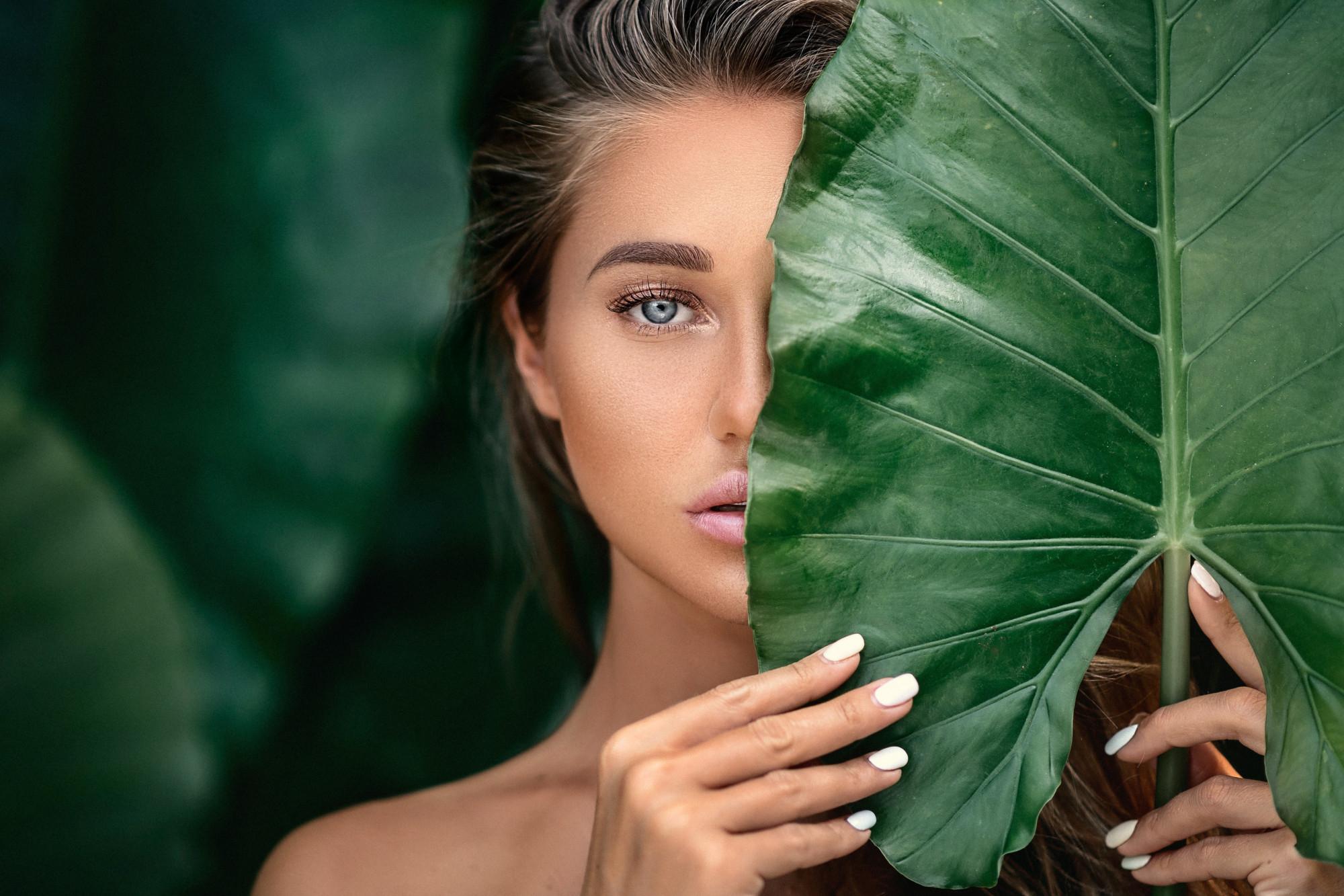 luxe portret van een mooie jonge vrouw met natuurlijke make-up houdt een groot groen blad half voor haar gezicht met een wazige blik